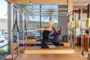 Pilates Instructor Kiera Goetz teaching Prenatal Pilates on the Cadillac thigh stretch with back extension